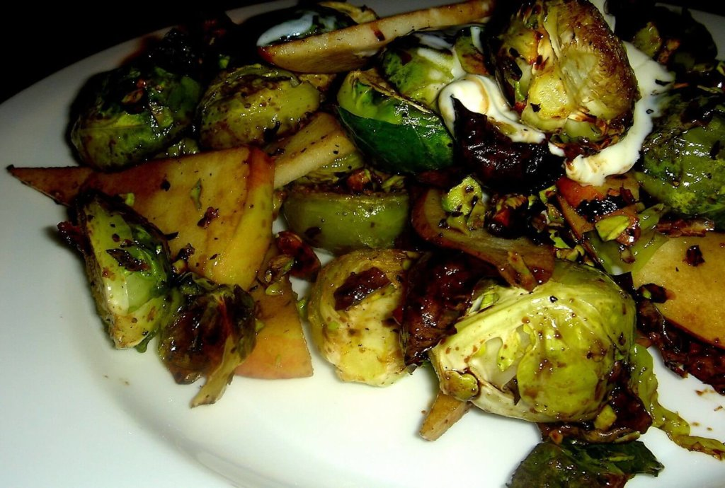 """Charred Brussels sprouts, sweet apples, sour crème fraîche and toasted pistachios combine to form a delicious mixture of contrasting flavors and textures in this """"Alta"""" tapas recreation. A balsamic vinegar reduction offers an at once sweet and sharp bite. // alexandracooks.com"""