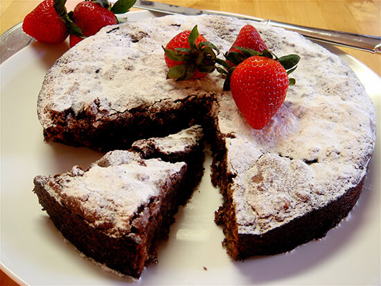 """This rich Passover chocolate cake rises dramatically, cracks and then falls. When dusted with Passover """"confectioners' sugar"""" and garnished with berries, the cake looks striking on the table. // alexandracooks.com"""