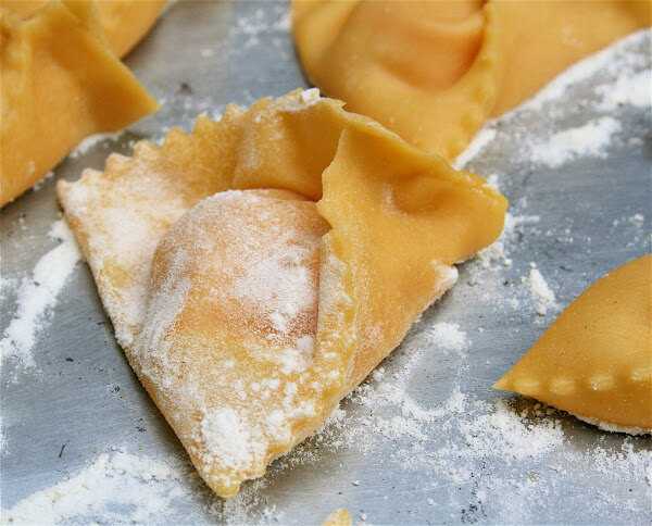 This pumpkin ravioli recipe can be made over a few days: Roast the squash and make the filling one day; make the dough and shape the ravioli the next; cook them immediately or freeze them indefinitely. The sage brown butter sauce takes no time to prepare, so having these tasty pillows on hand (frozen) makes for a simple dinner. And I guess they really can't be called ravioli. I'm not sure what shape they are, but they're yummy nonetheless. // alexandracooks.com
