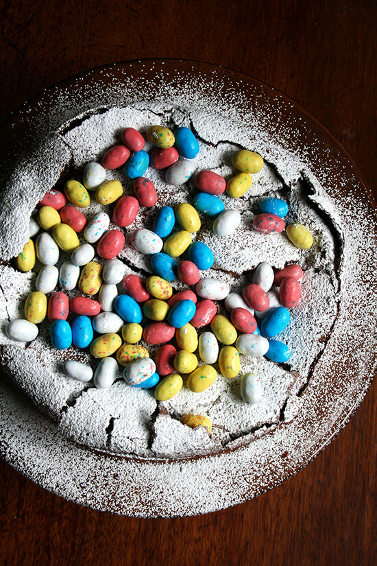 This rich chocolate Easter egg nest cake is festive and fun, puffing way up when it bakes and sinking when it cools, a crackly meringue-like layer forming a perfect base to house dozens of colorful candy eggs. // alexandracooks.com