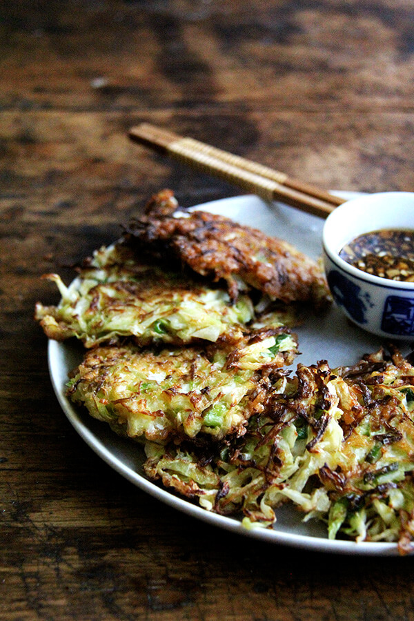Okonomiyaki, Japanese cabbage pancakes, can be made in countless ways: okonomiyaki essentially means prepared as you like. This my favorite version I've made yet, but know that you can add to it as you like with shrimp or chicken, sesame seeds or bonito flakes, other vegetables, etc. I prefer a soy-based dipping sauce to the more traditional mayonnaise-based, and, like the corn fritters, find these as irresistible freshly fried as cold straight from the fridge. // alexandracooks.com