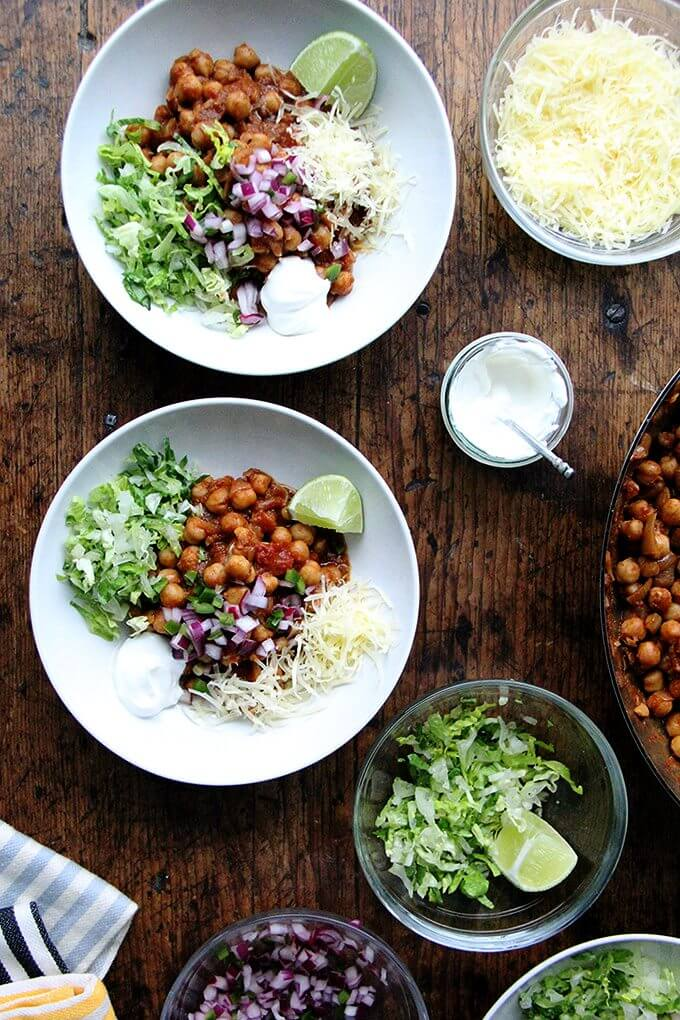 In these chickpea taco bowls, the chickpeas swell with the smoky, spicy, earthy flavors of the chili powder, cumin, crushed tomatoes, and garlic. Sweat the onions, add the seasonings, liquid, and protein, and simmer till flavorful. Yum. // alexandracooks.com