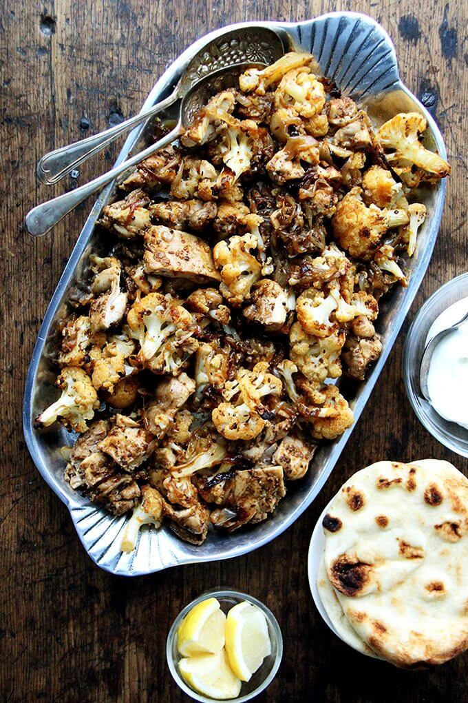"Heres the gist of this sheet pan chicken and cauliflower ""shawarma"": cauliflower florets, a sliced onion, and a few unpeeled  garlic cloves dressed with olive oil and a few thyme sprigs roast for 40 minutes on a sheet pan, where they caramelize before they meet a showering of salty, grated parmesan. The combination of sweet and salty, as you can imagine, is incredibly delicious. // alexandracooks.com"