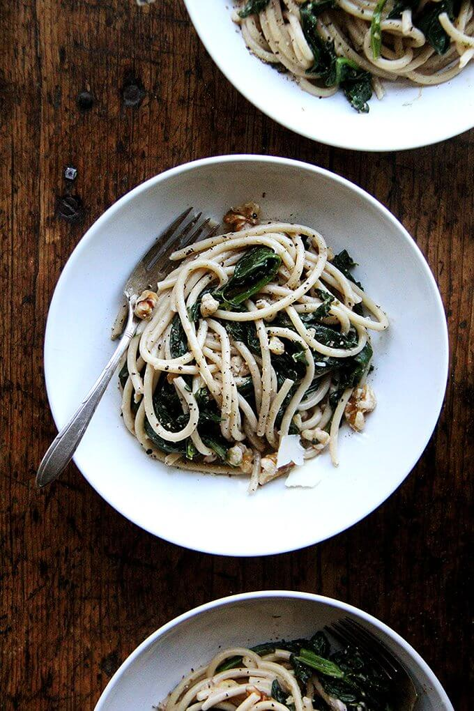 This pasta with spinach, walnuts, and lemon includes fresh greens tossed with a garlicky, white wine sauce made slightly creamy with crème fraîche. Yum. // alexandracooks.com