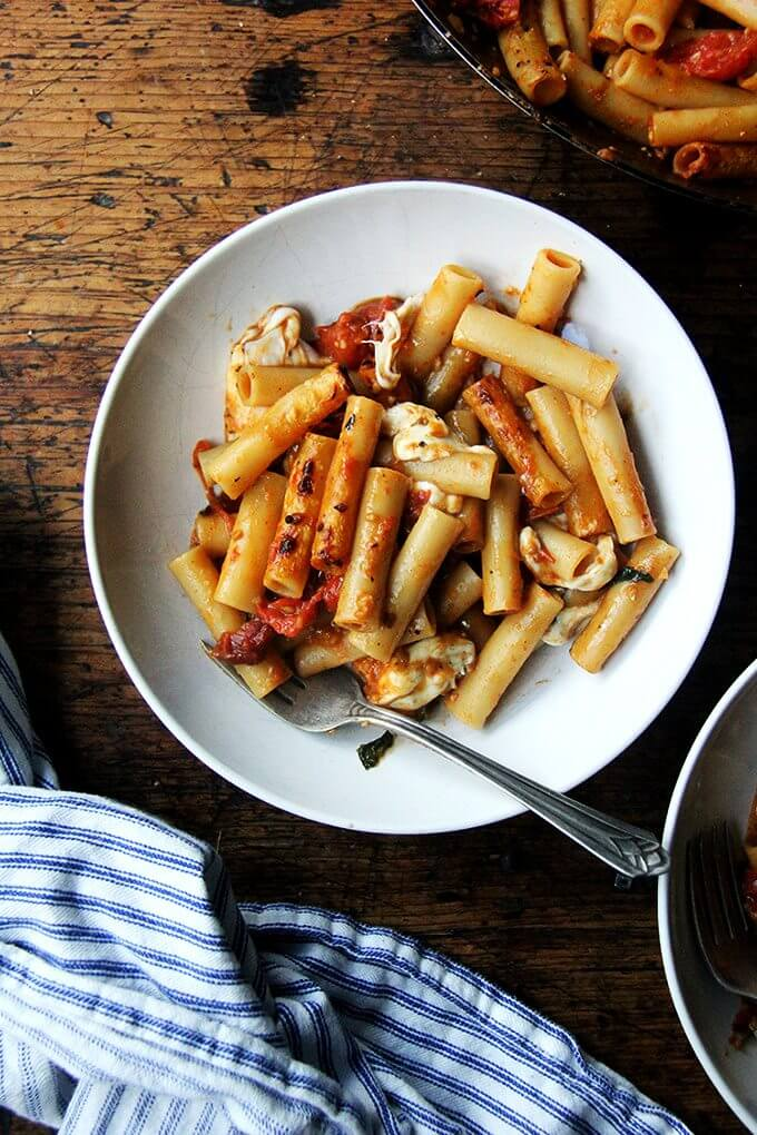 This one-pan baked ziti recipe has the added bonus of being a one-pot wonder: after you crush the tomatoes with a potato masher (or whisk or spoon), you add the dried pasta and water directly into the pan and simmer everything together until the pasta is cooked and the liquid has evaporated. In just about five minutes, your one-pan, no-fuss baked ziti is done: crisp noodles, melty cheese, bubbly sauce. // alexandracooks.com